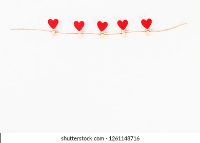 Valentine day layout. Red hearts on wooden clothespins on a jute twine on a white background. St. Valentines Day, day love, February 14 concept. Copy space, top view, flat lay composition