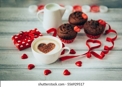 Valentine day love beautiful. Morning coffee, hearts and muffins on wooden background