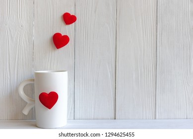 Valentine Day with red cup coffee Sewed pillow hearts row border, wood white background, copy space Valentine Concept.