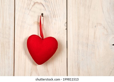 Valentine day. red fabric heart hung on wooden wall
