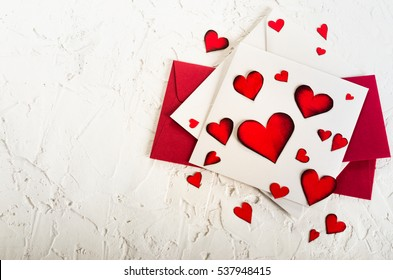 Valentine day. Red hearts and envelopes on white concrete background. Free space for your text.