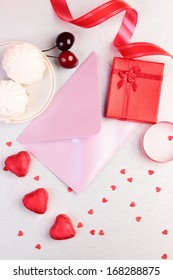 Valentine day still life with gift box, candies, ribbon and decorations