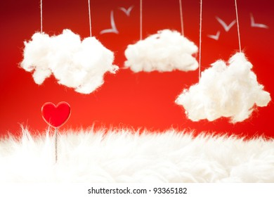 Valentine day theme with red heart on a spring clouds from cotton wool