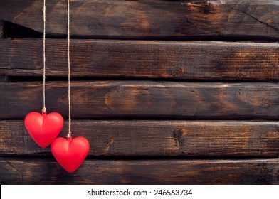 Valentine day. Two red heart pendant on a background of wood. Valentine's Day. Heart pendant. Red heart.  Space for text. Eighth of March. International Women's Day.