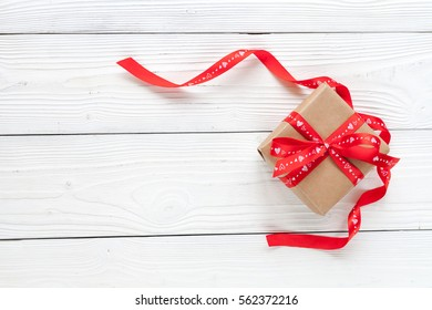 Valentine day wood background with gift and red ribbon.