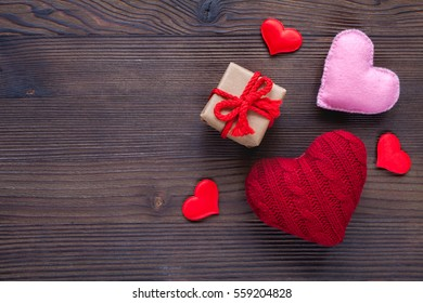 Valentine day wood background with red hearts and gift, top view