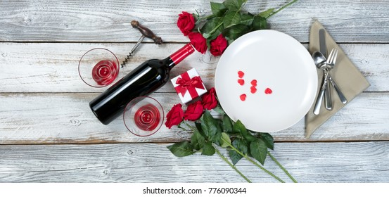 Valentine dinner setting with gift, red roses, wine and heart shapes on rustic table