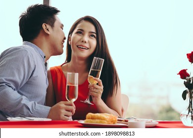 Valentine festive date at restaurant concept. Smile adult asian lover couple man and woman hand hold a champagne drink. Romantic dinner at restaurant