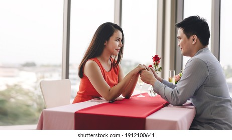Valentine festive date at restaurant concept. Smile adult asian lover couple man and woman hand hold together. Romantic dinner at restaurant