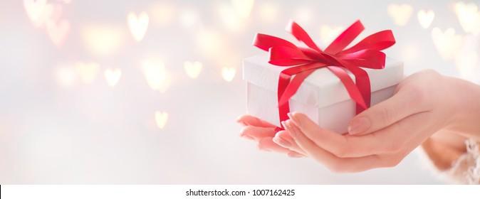 Ystävänpäivä lahja. Kauneus Nainen kädet tilalla Lahja laatikko punainen keula yli loma tausta hehkuva sydämet bokeh, lähikuva. pastellivärit. Laajakulman taustan muoto