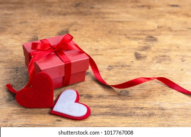 Valentine gift box with red heart on rustic wooden table and copy space. Small gift box concept.
