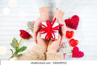 Valentine Gift. Young Couple Hands holding gift box with red bow gift over wooden background. St. Valentine's Day, Love concept. Top view, tabletop. Hands in Hands, romance, dating concept, top view