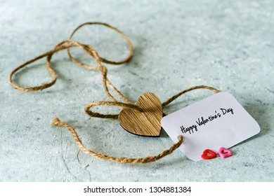 A Valentine greeting card, and wooden heart on delicate background.