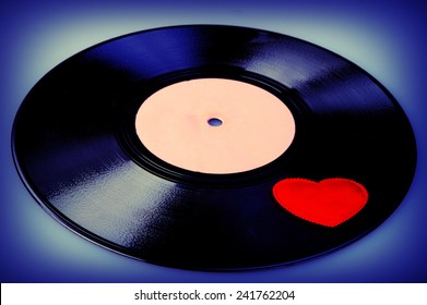 valentine heart lies on the old vinyl record