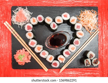 Valentine heart shaped sushi dinner table setting. Flatlay closeup of maki sushi rice rolls with salmon, tuna and eel fish (maki sake, maguro, unagi) in nori seaweed wrap. Stone dish, red table cloth.