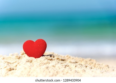 Valentine and Marry Concept. Sigle red hearts couple lovers for married on the sand summer beach, blue background