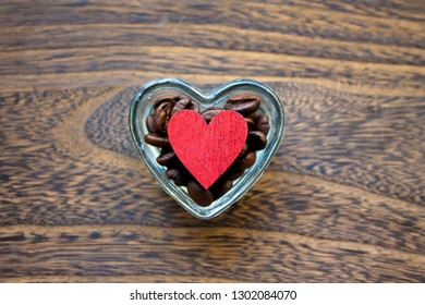 Valentine mood: coffee beans and heart shape in the little transparent porringer on wood background