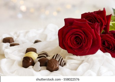 Valentine red roses and chocolate on white fabric with sparkling background, valentine concept.