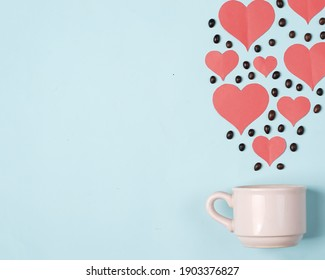 Valentine's background concept with coffee lovers. Combination of a white cup with coffee beans and a heart shaped cut of paper. Template design. Let's celebrate Valentine's Day by enjoying coffee.