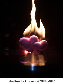 Valentines background. Valentine's Day heart on a dark wooden table. Burning hearts. Heart in fire. Dark toned foggy background. Selective focus