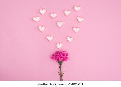 valentines candy with carnation flower on pink background minimal style
