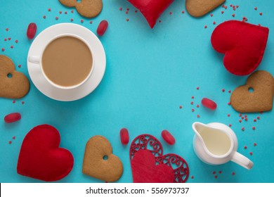 Valentine's card and concept. Cup of coffee with milk, red heart, sweets on blue background.  Top view.