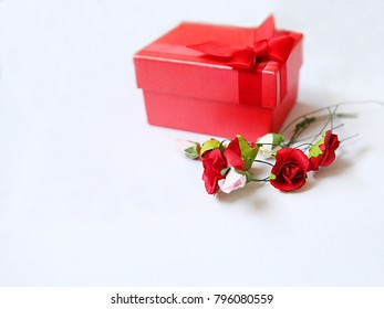 A Valentine's card with a Valentine's Day text and a gift with bouquet of roses.