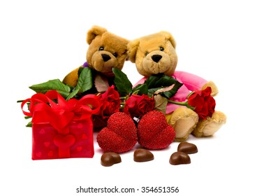 Valentine's composition with two snugly teddy bears, roses, chocolaty candy, gift box and hearts on white background.