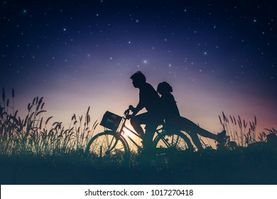 Valentines concept, Romantic couple in love with their bicycle on field,dreaming about the stars in night sky.