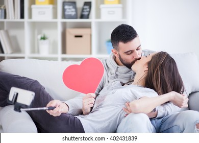 Valentines couple making selfie and sharing cardboard heart and love,small depth of field