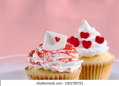 Valentine's cupcakes for two.  One with a fondant topping depicting an envelope decorated with a heart, another with red candies