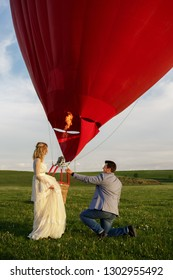 Valentine's Day. Amazing marriage proposal. Young man makes a proposal to get married near red hot air balloon