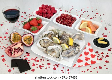 Valentines day aphrodisiac food and drink selection which can promote good sexual health forming a background over distressed white wood.