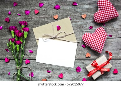 valentines day background. blank white greeting card with purple carnation flowers and envelope with gift box and handmade hearts on rustic wooden background. top view. mock up