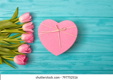 Valentine's Day background with bouquet of tulips and a gift box in the shape of a heart.