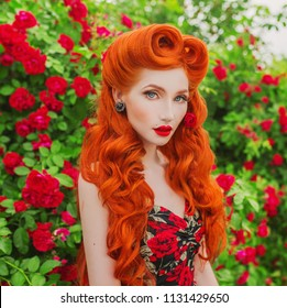 Valentines Day background. Brilliant retro girl with red lips in stylish dress with print of roses in beautiful summer garden. Redhead model with brilliant hairstyle on background of bush of roses.