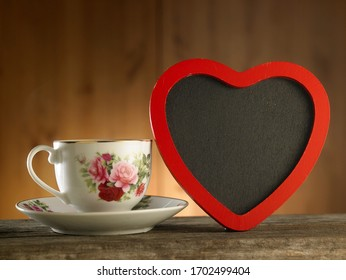 Valentines day background. Cup of coffe and heart shape blackboard for copy space