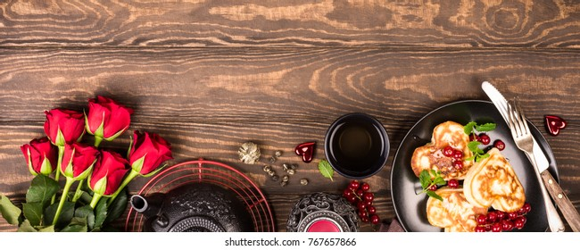 Valentine's day background with delicious pancakes in form of heart, green tea, black teapot, candles and roses. Valentines day concept greeting card. Top view. Copy space. Banner.