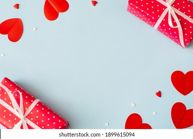 Valentine's Day background February 14th. Gifts, confetti, red hearts of paper on pastel blue background. Valentines day concept. Flat lay, top view, copy space.