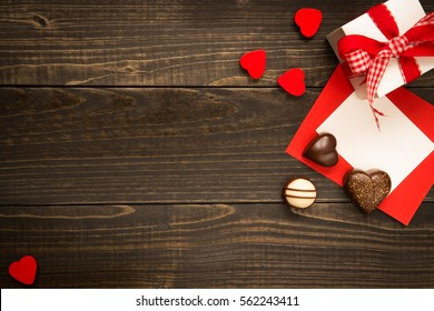 Valentine's Day background. Gift box, red hearts and Valentine's day card with copy space on the wooden dark desk.
