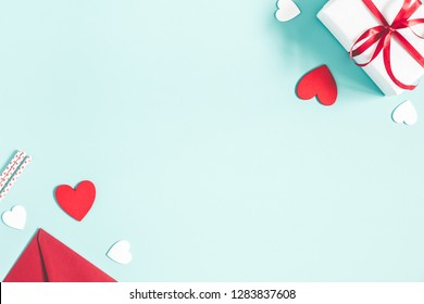 Valentine's Day background. Gifts, candle, confetti, envelope on pastel blue background. Valentines day concept. Flat lay, top view, copy space