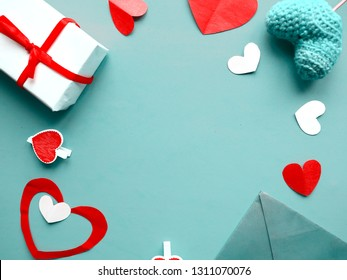 Valentines Day background. Hand made hearts and red giftboxes on blue background. Flat lay, top view, copy space