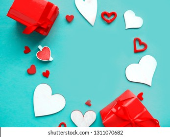 Valentines Day background. Hand made wooden hearts and red gift boxes on blue background. Flat lay, top view, copy space