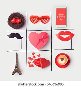 Valentine's day background with heart shape and party accessories. Tic tac toe game concept. View from above. Flat lay