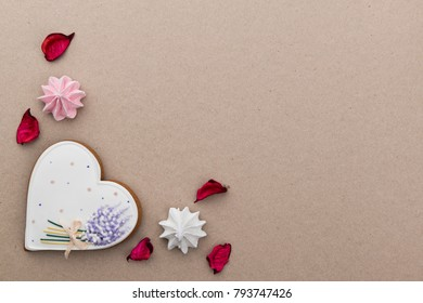 Valentines day background with heart shaped gingerbread cookie, marshmallows and rose petals on craft paper