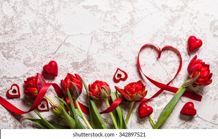 Valentines Day background with hearts and red tulips