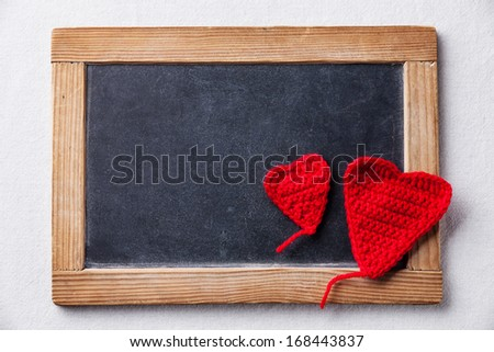 Valentine's day background with Knitted red hearts and Vintage slate chalk board