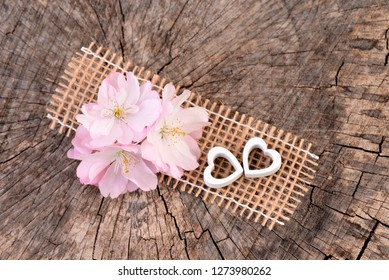 Valentines Day background with pink cherry - flowers. Valentines card with heart, old wooden background.