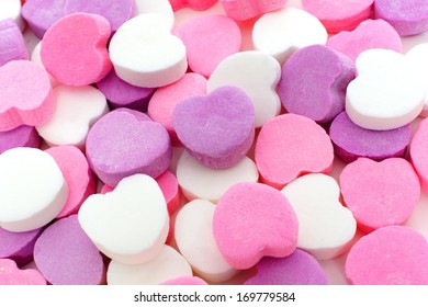 Valentines Day background of pink, purple and white candy hearts