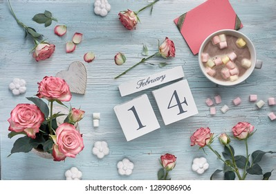 Valentines day background with pink roses, wooden calendar, greeting card and decorations, flat lay